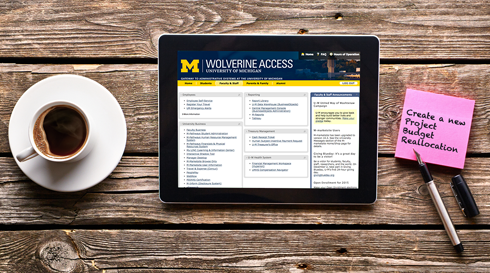 IPad loged into U-M Wolverine Access with cup of coffee next to it.